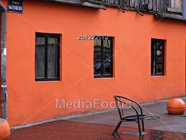 Old House Painted In Neon Orange Color With Reflections In Windows. Stock Photo