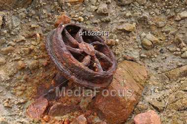 Old Iron Wheel From A Coal Wagon Buried In A Rocky Outcrop On A West Coast Beach, New Zealand Stock Photo