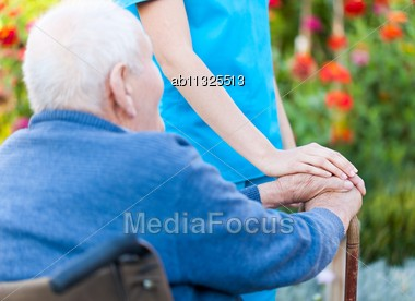 Old Man Holding His Stick, Sitting In Wheelchair Stock Photo