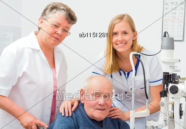 Old Man With Nurse And Doctor At An Optical Exam Stock Photo