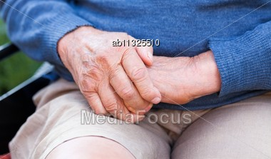 Old Man Sitting In Wheelchair, Warming Up His Hands Stock Photo