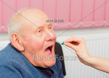 Old man suffering from dementia taking daily treatment from his nurse. Stock Photo