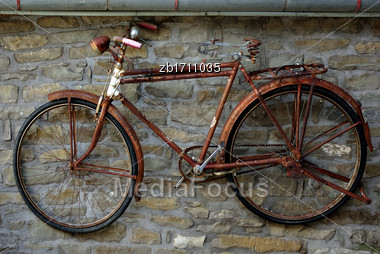 Old Rusty Bicycle Hanging On Stone Wall Stock Photo