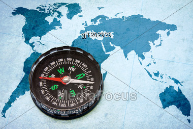 Old Scratched Compass On The Blue World Map Stock Photo