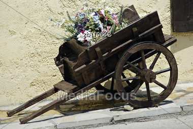 Old Small Wooden Coach Full Of Summer Flowers At Sunny Day Stock Photo