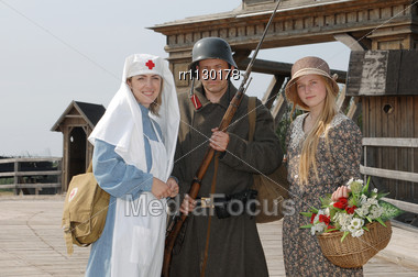 Old Style Picture With Woman In Nurse Costume, Her Daughter In Flowered Dress And Man In Soldier Uniform With Weapon. Costumes Are Authentic To The Ones Weared In Time Of World War I Stock Photo