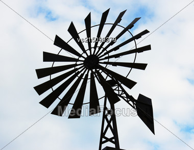 Old Water Pumping Windmill. Windmill Water Tower On Sky Background. Dark Silhouette Of Farm Windmill Stock Photo
