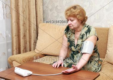 Old Woman Measures Arterial Pressure In Room Stock Photo