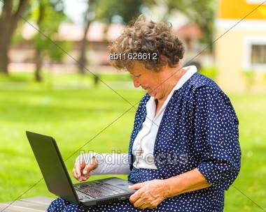 Old Woman Typing With Her Broken Arm On Her Laptop To Order And Shop From The Internet Stock Photo