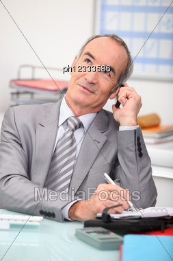 Older Businessman Using A Cellphone Stock Photo