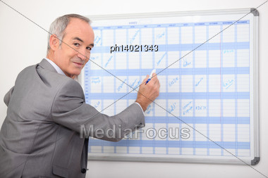 Older Businessman Writing On A Wall Planner Stock Photo