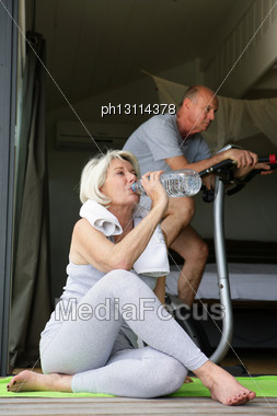 Older Couple Exercising At Home Stock Photo