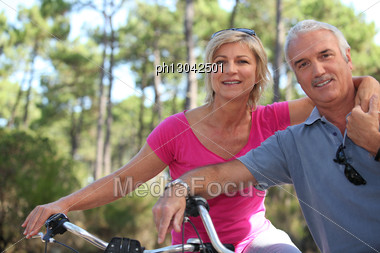 Older Couple Riding Bikes Stock Photo