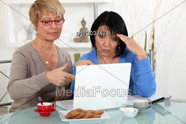 Older Women Puzzling Over A Laptop Stock Photo