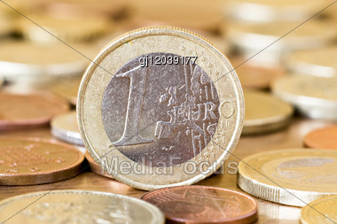 One Euro Coin In A Middle Of Other Coins Stock Photo