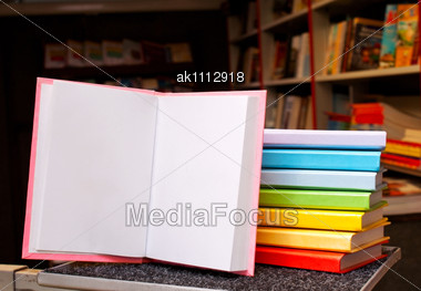 Open Book With A Stack Of Colorful Books Behind Stock Photo