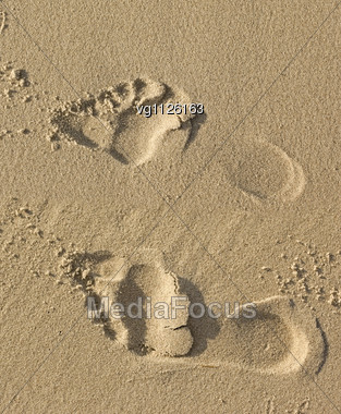 Optical Illusion Footprints On The Sand With Shadows, Summer Vacation Concept Stock Photo
