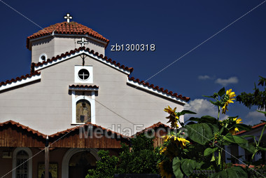Orthodox Church At Sunny Summer Day With Clear Blue Sky And With Sunflower In Front. Stock Photo
