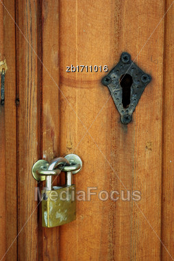 Padlock On Old Wooden Door With Black Keyhole Stock Photo