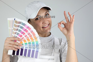 Painter Giving The A-ok Sign And Holding A Palette Of Colour Samples Stock Photo