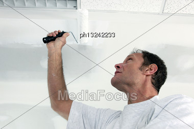 Painter Using Roller On Ceiling Stock Photo