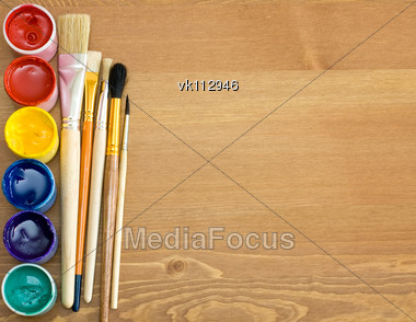 paints and brushes on wooden table Stock Photo