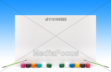 Paints With Paintbrushes And Paper On Blue Background Stock Photo