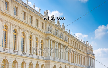 Palace Side With Statues On Top In Versailles Over Blue Sky. France Stock Photo