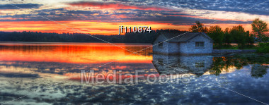 Panorama Of A Sunrise And Pump House Utility On A Lake Stock Photo