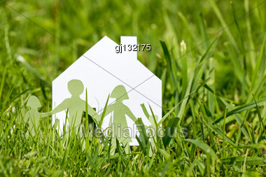 Paper Cut Of Family With House In A Green Grass Stock Photo