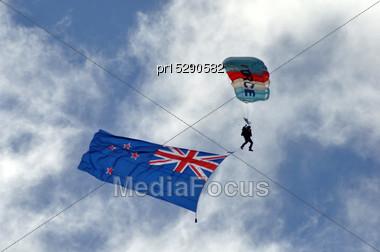 Parachutist Displays The New Zealand Flag At An Airshow Stock Photo