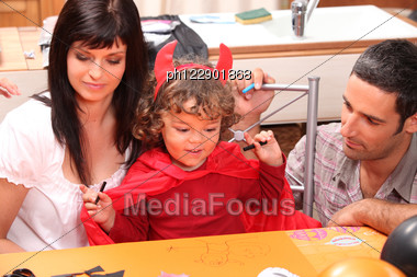 Parents And Son Preparing Halloween Party Stock Photo