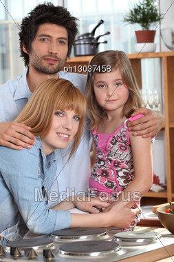 Parents And Their Daughter In The Kitchen Stock Photo