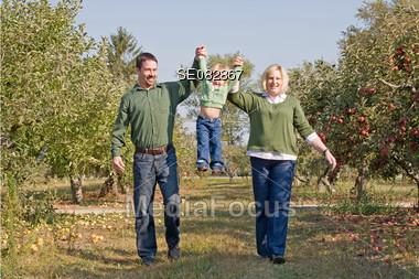 Parents Swinging Little Girl Stock Photo