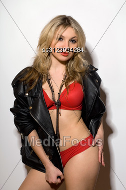 Passionate Young Blond Woman In A Red Lingerie And Black Leather Jacket Stock Photo