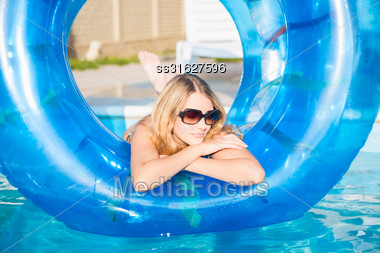 Pensive Blond Woman Posing With Rubber Ring In Swimming Pool Stock Photo