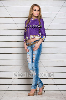 Pensive Blond Woman In Ripped Jeans And Purple Jacket Posing Near The White Wooden Wall Stock Photo