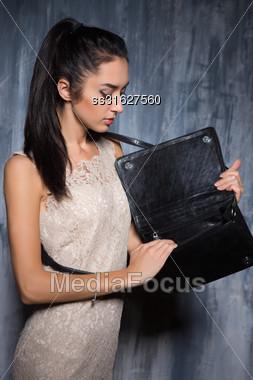 Pensive Brunette Wearing White Dress Looking Something In Her Handbag Stock Photo