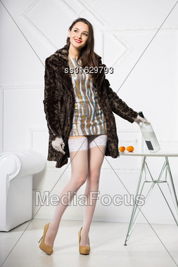 Pensive Woman Wearing Short Dress And Fur Coat Posing With Bottle Stock Photo