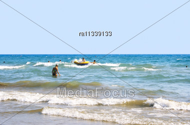 People Having Fun On Sea Waves. Stock Photo