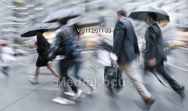 People Rushing On The Rainy Street In Intentional Motion Blur Stock Photo
