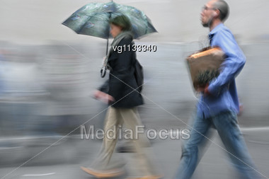 People Walking On The Rainy Street In Intentional Motion Blur Stock Photo