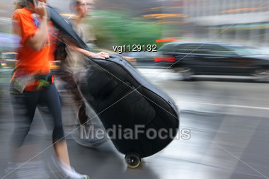 People Walking On The Street In Intentional Motion Blur, Female And Male Musicians Carrying Instrument In The Case Stock Photo