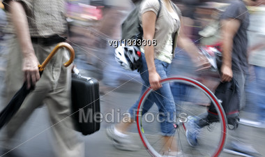 People Walking On The Street In Intentional Motion Blur, Woman Holding Spare Bike Wheel Stock Photo