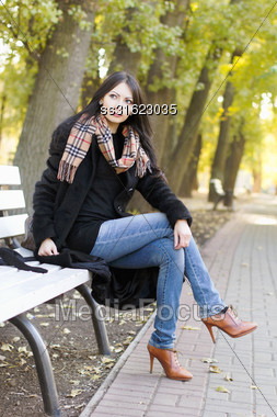 Perfect Young Woman Sitting On A Bench In Autumn Park Stock Photo