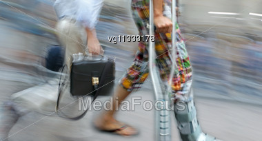 Person On Crutches Crossing Street In Intentional Motion Blur, Businessman Running By Stock Photo