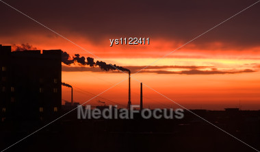 Photograph Of Industrial Buildings At Sunset Sky Stock Photo