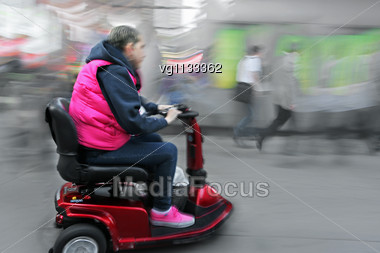 Physically Handicapped Female Person On A Power Mobility Scooter, Ability To Be Independent Concept Stock Photo