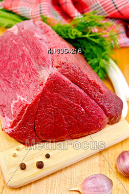 Piece Of Beef, Garlic, Peas Pepper, Dill, Chives, Napkin, Knife On A Wooden Board Stock Photo
