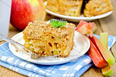 Piece Of Sweet Cake With Rhubarb And Apples, Mint, Blue Napkin, Cup On The Background Of Wooden Boards Stock Photo